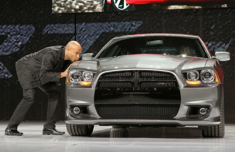 Image: President and CEO of Dodge, Ralph Gilles kisses the fender of the new Charger SRT8