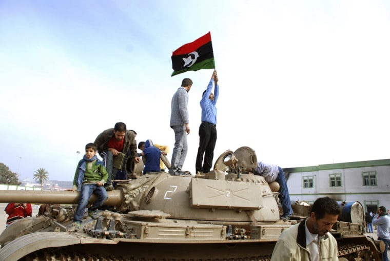 Image: Residents stand on a tank holding a pre-Gadhafi era national flag
