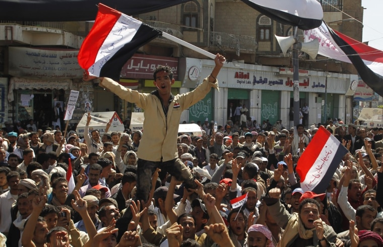 Image: Anti-government protesters carry a fellow protester during a protest outside Sanaa University