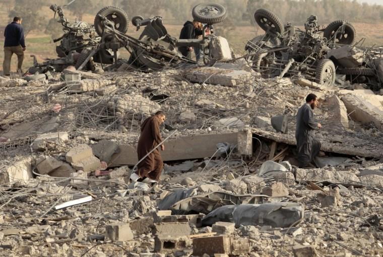 Image: People walk inside a destroyed weapons dump near Benghazi