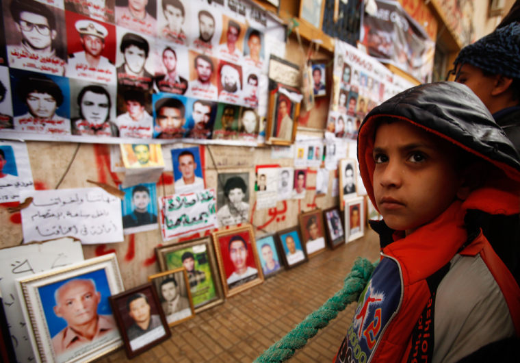 Image: Boy looks at pictures of missing and killed Libyans in a street in Benghazi