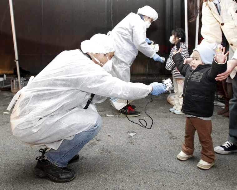 Image: Officials in protective gear check for signs of radiation on children who are from the evacuation area near the Fukushima Daini nuclear plant in Koriyama