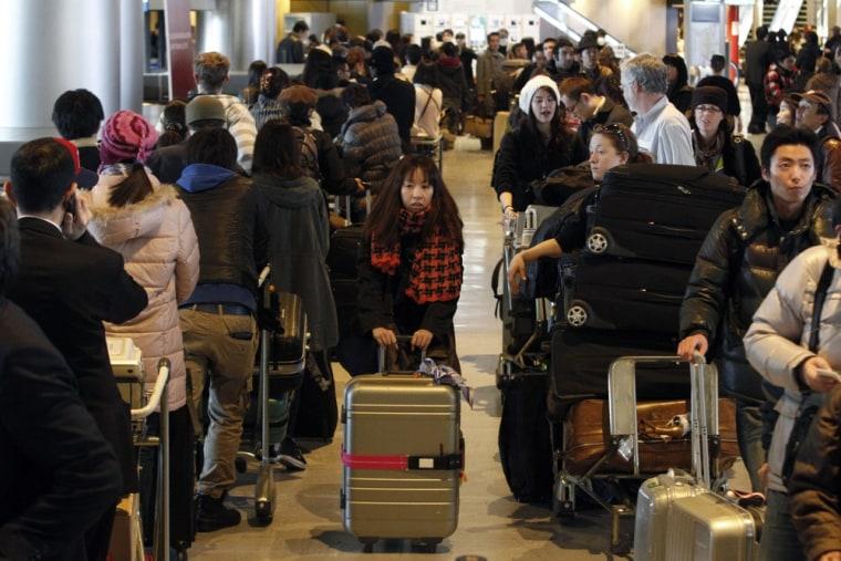 Image: Passengers queue at Narita airport
