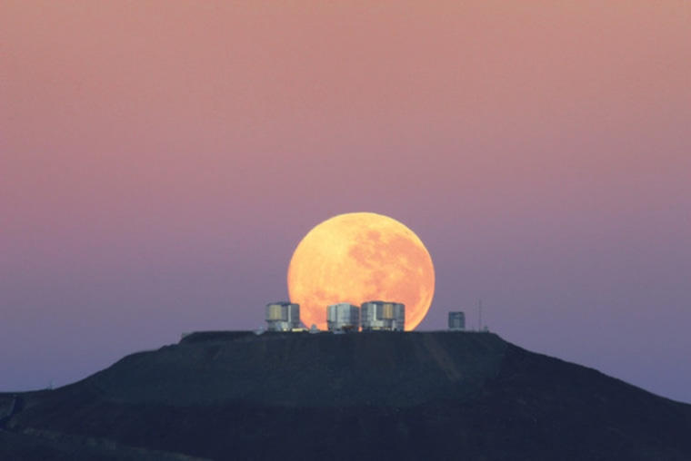 The dazzling full moon sets behind the Very Large Telescope in Chile's Atacama Desert in this photo released June 7, 2010, by the European Southern Observatory. The moon appears larger than normal because of an optical illusion of perspective.