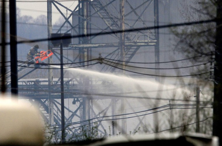 Image: A Louisville firefighter works to put out a fire after an explosion at the Carbide Industries plant