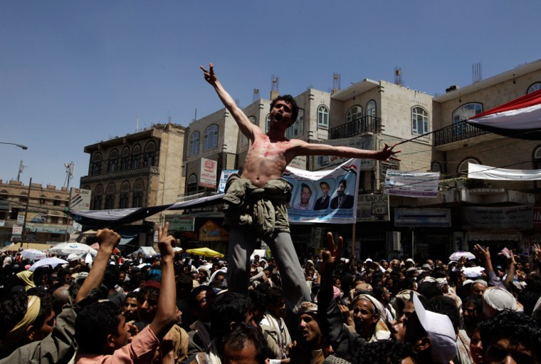 Image: Anti-government protesters shout slogans during a rally to demand the ouster of Yemen's President Ali Abdullah Saleh outside Sanaa