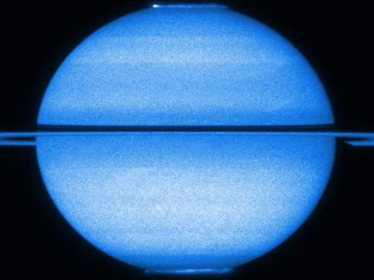 The Hubble Space Telescope shows Saturn with the rings edge-on and both poles in view, with both of its fluttering auroras visible, in early 2009.