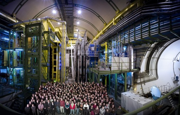LHCb team members stand in front of their experiment, the LHCb detector, at the Hadron Collider.