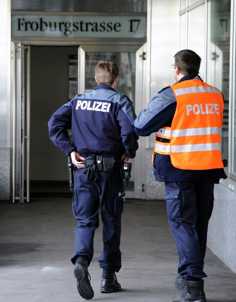 Image: Policemen stand in front of the entrance of Swiss nuclear power industry association, on March 31, 2011 in Olten. Two people were injured when a letter bomb exploded at the offices of the association.