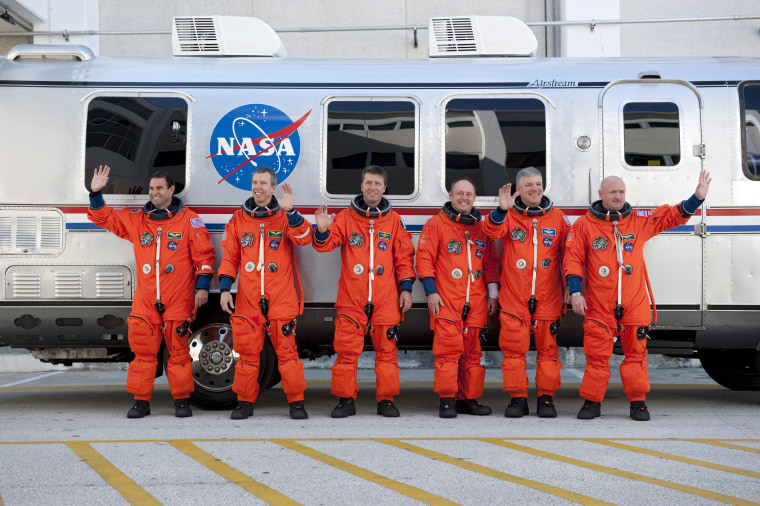 The STS-134 crew pauses for a photo before climbing onboard the Astrovan at NASA's Kennedy Space Center in Florida. As part of their preparations, the crew rides to Launch Pad 39A in the vehicle and strap intoEndeavour to practice steps that will be taken on launch day. From right to left are commander Mark Kelly, pilot Greg H. Johnson, mission specialist Mike Fincke, Roberto Vittori of the European Space Agency, and mission specialists Andrew Feustel and Greg Chamitoff.
