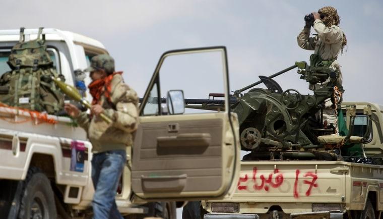 Image: A Libyan rebel uses his binoculars to sc