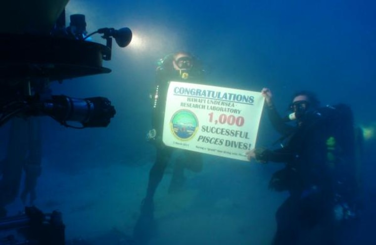 Divers Dave Pence, left, and Ken Longeneckerhold up a banner commemorating the Hawaii Undersea Research Laboratory's 1,000th dive with the Pisces submersible.