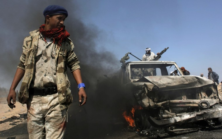 Image: Libyan rebels inspect two destroyed military vehicles of pro-Gadhafi forces that rebels claim were targeted by a NATO strike along the front line near Brega.