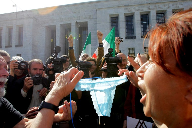 Image: A Berlusconi's supporter shows women's underwear outside the court in Milan, Italy, Wednesday,