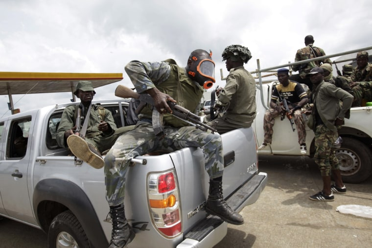Image: Soldiers loyal to Alassane Ouattara return from fighting, at a checkpoint serving as an operating base,