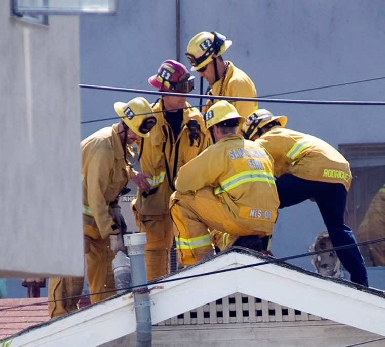 Image: Firefighters on the roof of a home