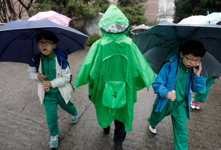 Image: South Korean students holding umbrellas go home amid fears that the rain may contain radioactive materials from the crippled nuclear reactors in Japan at Midong elementary school in Seoul