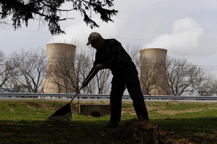 Image: A man rakes his son's front yard across from the Three Mile Island nuclear power plant