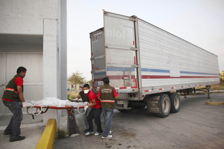 Image: Morgue employees take a body, found on Wednesday in a mass grave, from a refrigerated truck into the local morgue