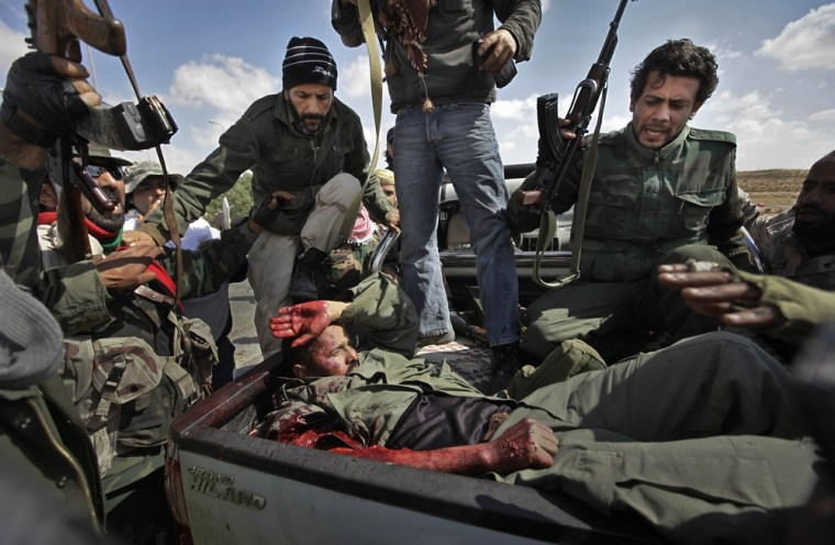 Image:  A wounded prisoner from Gadhafi's forces is transported in the back of a pickup truck by rebels