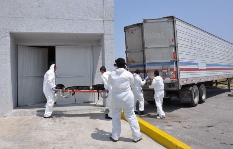Image: Forensic workers carry a body