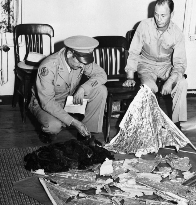 Brig. Gen. Roger M. Ramey, commanding general of 8th Air Force, and Col. Thomas J. Dubose, 8th Air Force chief of staff, identify metallic fragments found by a farmer near Roswell, N.M., as pieces of a weather balloon. This is the basis of the Roswell Incident, the supposed crash of an alien spacecraft.