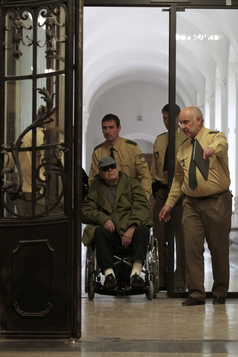 Image: Defendant John Demjanjuk (C, in the wheelchair) arrives for another session of his trial on April 13, 2011 in Munich, southern Germany.