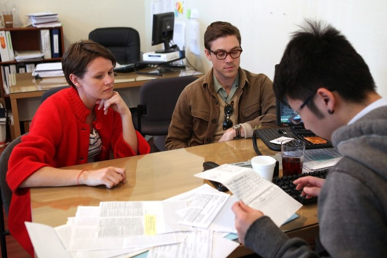 Image: Drew Darmon and his wife Erika Darmon receive tax preparation assistance from a preparer
