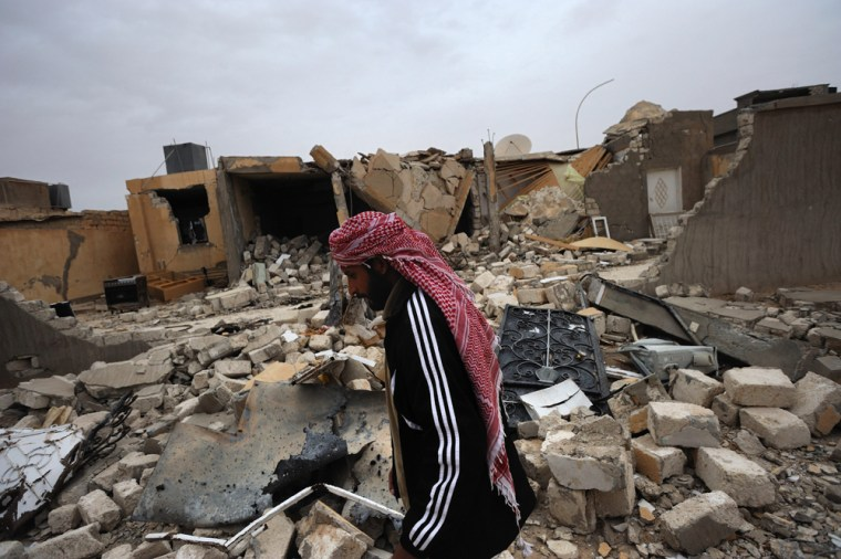 Image: A Libyan man walks past a house allegedly destroyed by Gaddafi's army in the town of Ajdabiya