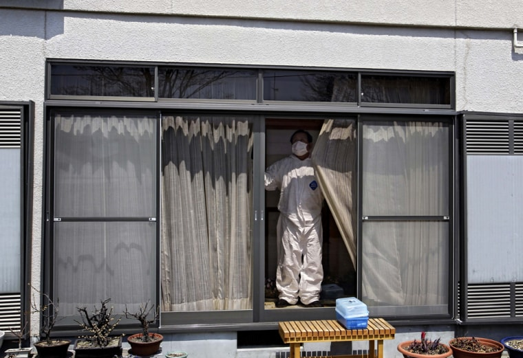 Image:A man, wearing a protective suite, shuts the curtains of a house in the deserted town of Futaba, inside the 20-kilometer (12-mile) evacuation zone, in Fukushima Prefecture, Japan