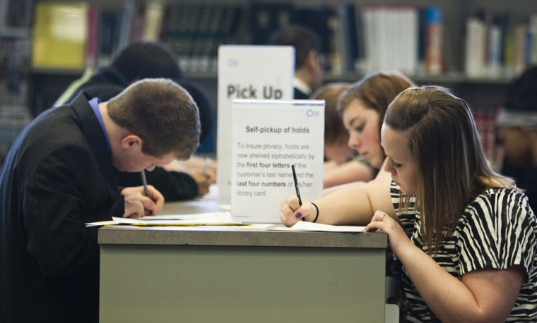 Image: job seekers fill out job applications at a teen job fair held at the Swanson Public Library in Omaha, Neb.