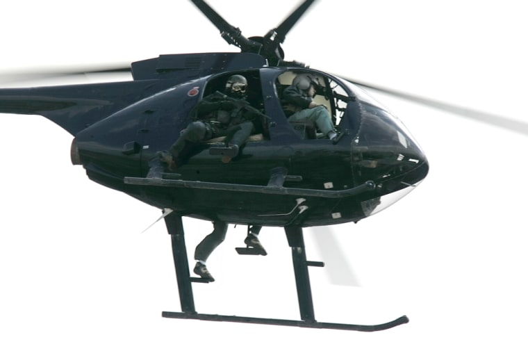 Image: A helicopter operated  by Blackwater USA, a private security contractor, flies over central Baghdad, Iraq