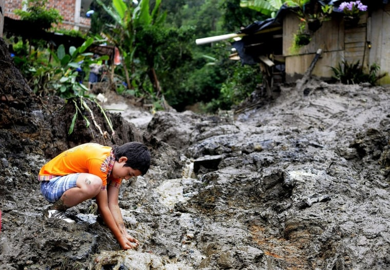 Image: A boy plays in the middle of a landslide in Sabaneta town north west of Colombia, on 25 April.
