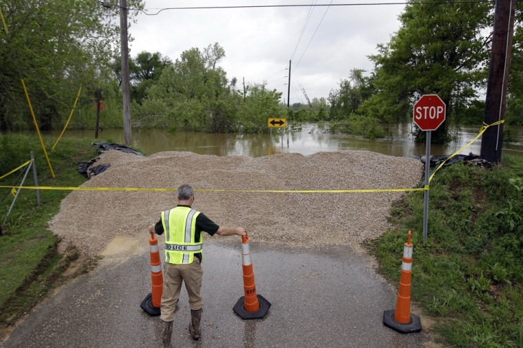 Image: Detective Corey Mitchell with the Poplar Bluff Police Department adjusts traffic cones near a temporary levee holding back water from the Black River