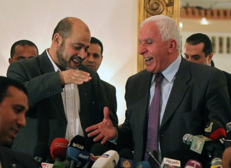 Image: Palestinian Fatah delegation chief Azzam al-Ahmed (R) shares a laugh with Hamas deputy leader Mussa Abu Marzuq (L) as they prepare to shake hands after a joint press conference in Cairo on April 27.