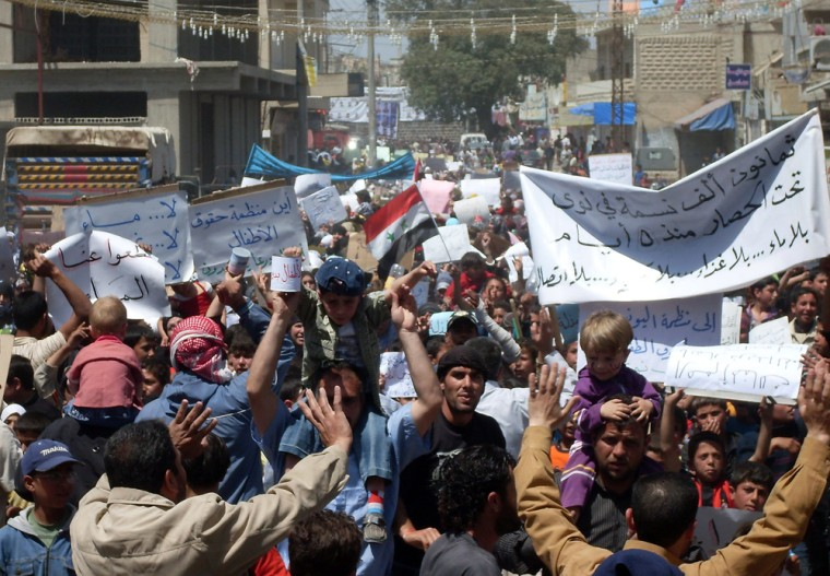 Image: Syrian anti-government protesters hold banners calling for an end to a military siege in Nawa near the southern town of Daraa on April 28.