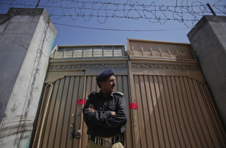 Image: A policeman stands guard outside one of two gates of the compound where al Qaeda leader Osama bin Laden was killed in Abbottabad