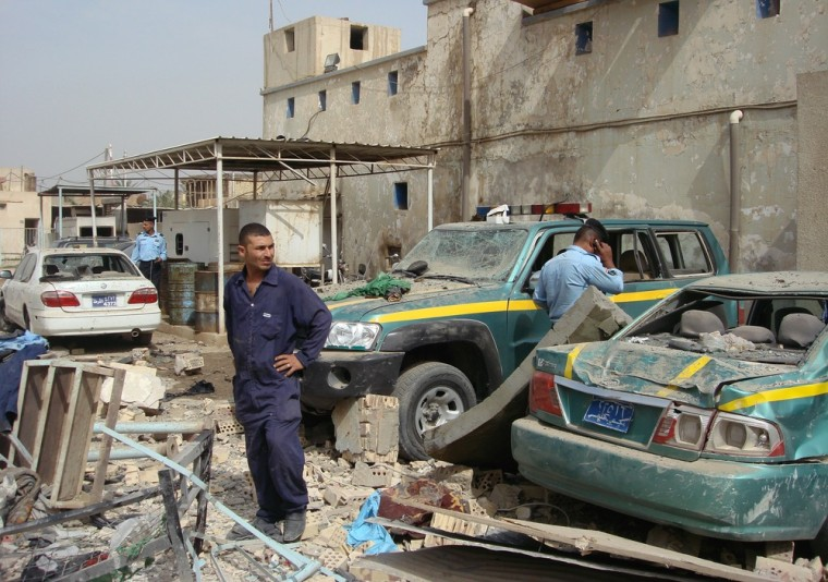 Image: A member of the civil defence and policemen inspect the site of a bomb attack in Hilla, Iraq.