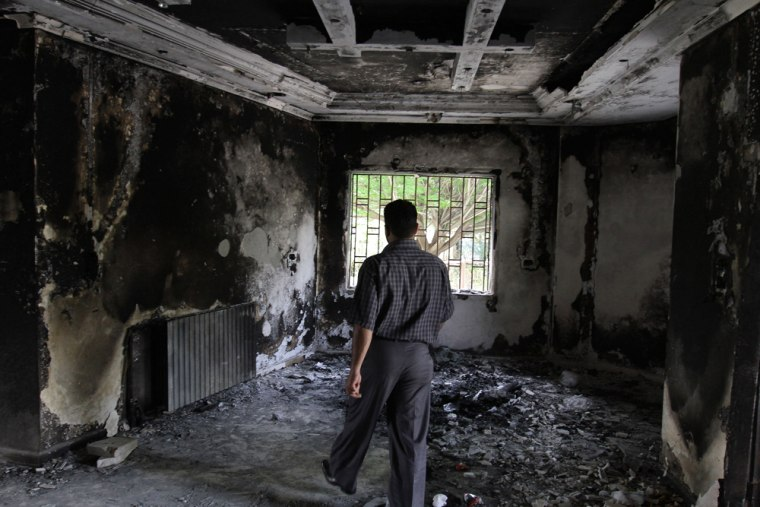 Image: In this photo taken on a government tour, a Syrian man walks through a burnt house in the southern Syrian protest hub of Daraa
