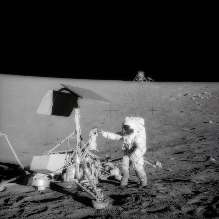 A television camera and several other pieces were taken from Surveyor 3 and brought back to Earth for scientific examination. Here, Apollo 12 moonwalker Pete Conrad examines the Surveyor's TV camera before detaching the gear.