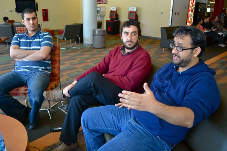Mohamed Elcataani, right,president of the Libyan Student Union at Washington State University, discusses the impending loss of scholarship funds following the U.N. freeze of Libyan government assets.With him Abdalhamid Alkar, left,and Mohamed Elhess.
