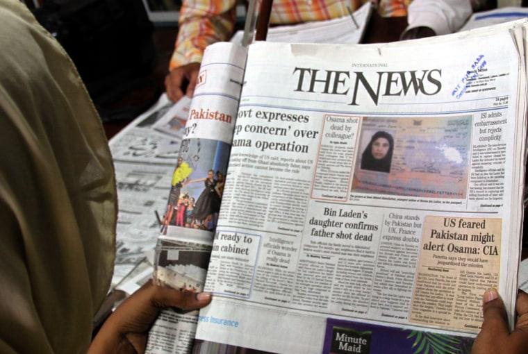 Image: A woman reads a newspaper showing the passport of Amal Ahmed al-Sadah, Osama Bin Laden's Yemeni wife