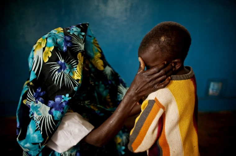 Image: A mass rape victim comforts her son in the town of Fizi, Congo.