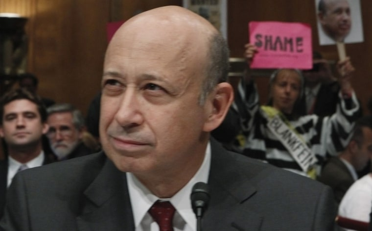 Image: Protesters hold up signs before Goldman Sachs Chairman and CEO Lloyd Blankfein testifies on Capitol Hill