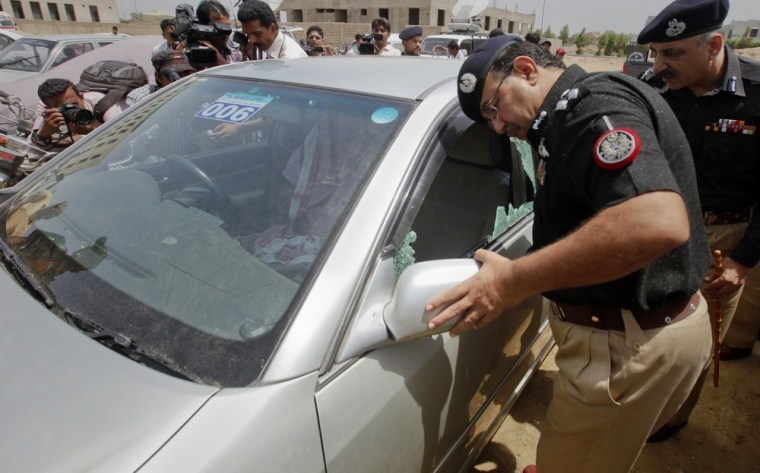 Image: Policemen inspect a damaged car in which a Saudi diplomat was travelling in when under attack by gunmen, in Karachi