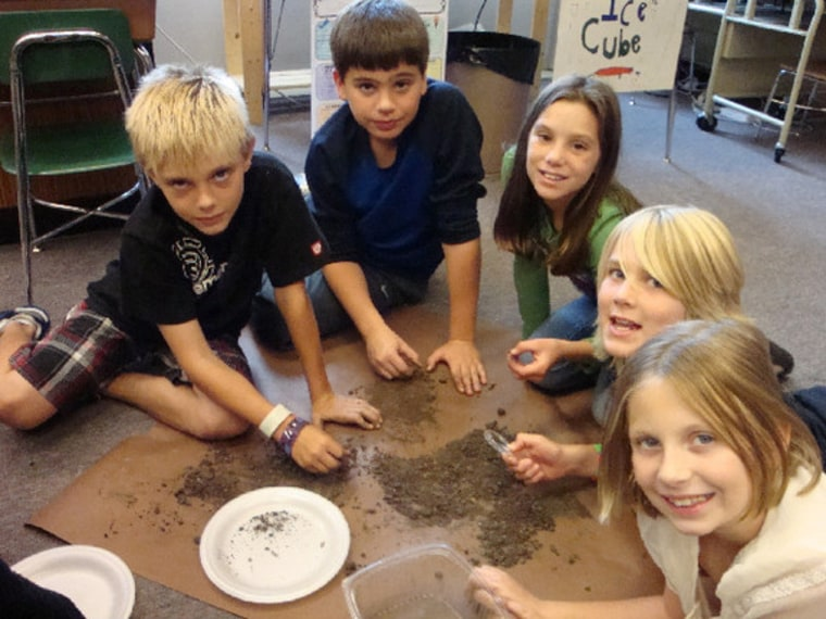 Fourth-grade scientists in action, sifting through dirt from a mastodon excavation.