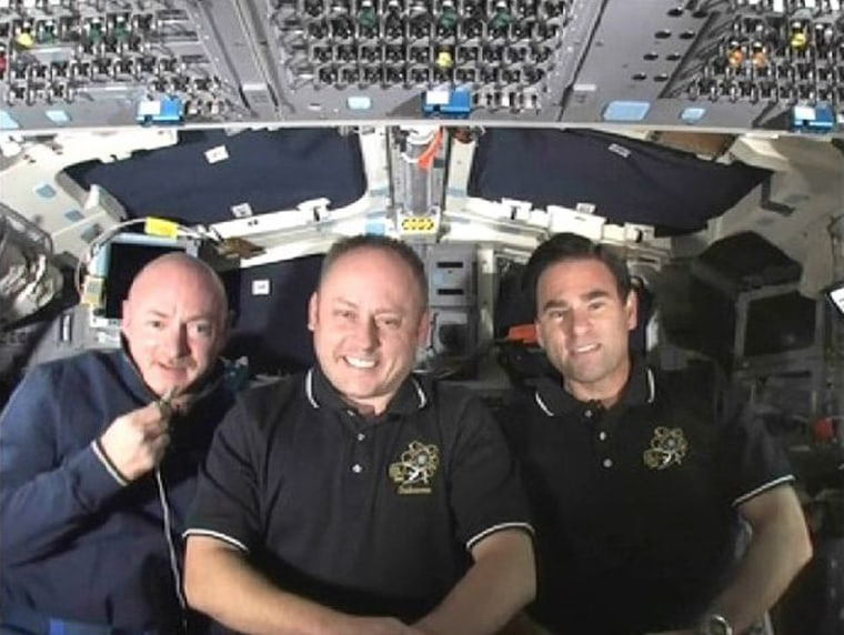 Image: Commander Mark Kelly  is joined by astronauts Michael Fincke and Greg Chamitoff  from the aft flight deck of the Endeavour