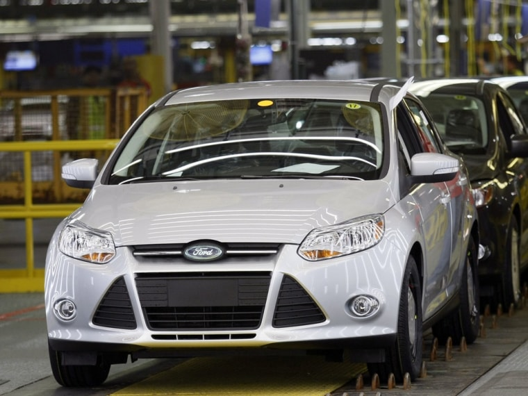Image: A Ford Motor assembly worker watches new 2012 Ford Focus vehicles move along the final production line at Michigan Assembly Plant in Wayne