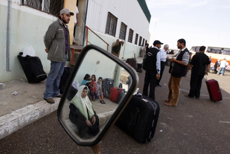 Image: Palestinians wait to cross into Egypt through the Rafah border crossing in the southern Gaza Strip