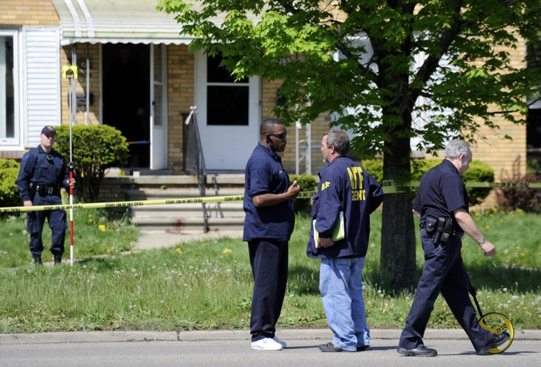 Investigators at the scene of a shooting in Detroit on May 3, 2010 where police responding to a 911 call at a vacant house in Detroit were met with heavy gunfire that killed one officer and wounded four others. It was the first time in five years that a Detroit police officer has been killed in the line of duty.